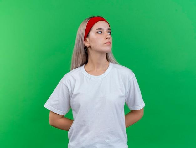 머리띠를 착용 중괄호와 자신감 젊은 백인 스포티 한 소녀