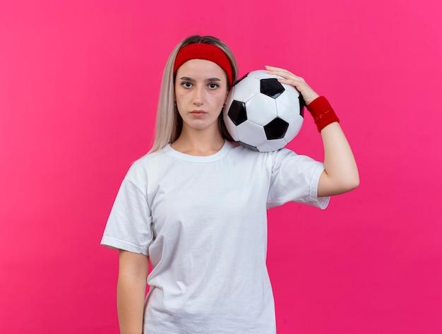 Уверенная молодая кавказская спортивная девушка с подтяжками в головной повязке