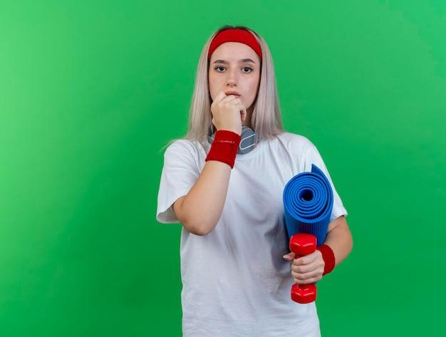 Fiduciosa giovane ragazza sportiva caucasica con le parentesi graffe che indossa la fascia Foto Gratuite