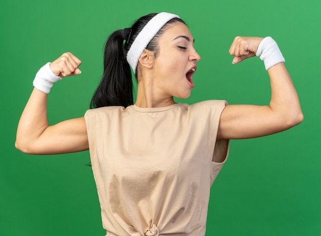 머리띠와 팔찌를 착용한 자신감 넘치는 젊은 백인 스포티 여성은 녹색 벽에 격리된 그녀의 근육을 바라보며 강한 몸짓을 하고 있다