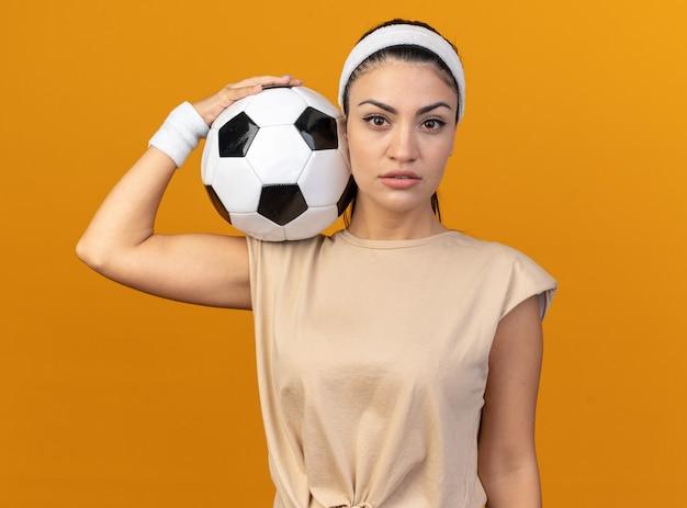 Confident young caucasian sporty woman wearing headband and wristbands holding soccer ball on shoulder looking at front isolated on orange wall