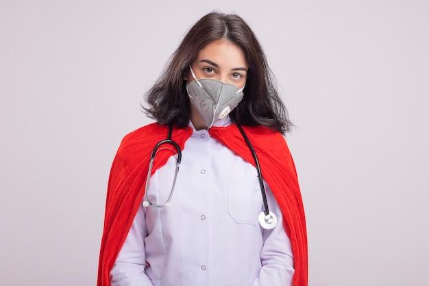 コピースペースと白い壁に分離された保護マスクと医師の制服と聴診器を身に着けている赤いマントの自信を持って若い白人のスーパーヒーローの女の子