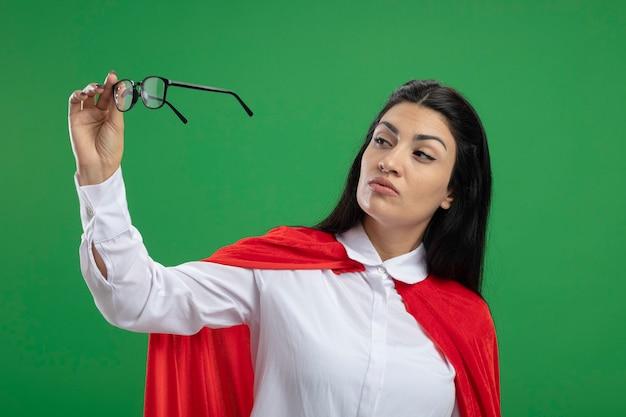 Fiduciosa giovane ragazza indoeuropea supereroe guardando gli occhiali che tiene in mano isolato sulla parete verde