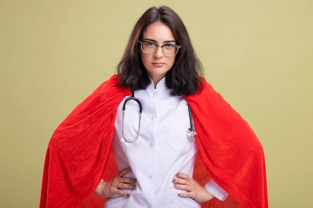 Fiducioso giovane supereroe caucasica ragazza in mantello rosso che indossa l'uniforme del medico e lo stetoscopio con gli occhiali che tengono le mani sulla vita