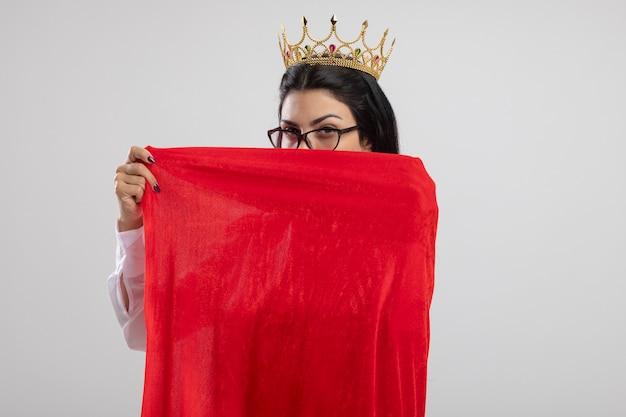 안경과 왕관을 쓰고 자신감이 젊은 백인 슈퍼 히어로 소녀 복사 공간이 흰 벽에 고립 된 뒤에서 얼굴을 덮고 그녀의 영웅 케이프를 잡는 왕관