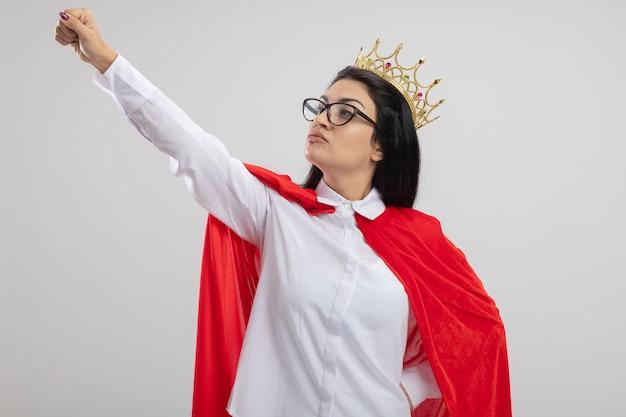 Уверенная молодая кавказская девушка супергероя в очках и короне держит руку на талии, поднимая кулак, глядя на свой кулак, изолированные на белом фоне