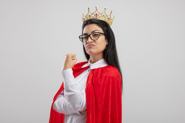 Уверенная молодая кавказская девушка супергероя в очках и короне, стоящая в профиле, глядя на камеру, сжимая кулак, изолированную на белом фоне с копией пространства