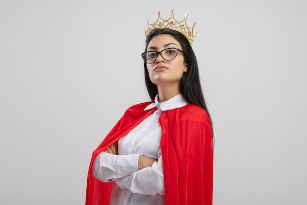 Уверенная молодая кавказская девушка супергероя в очках и короне, стоящая с закрытой позой в профиль, глядя в камеру, изолированную на белом фоне с копией пространства