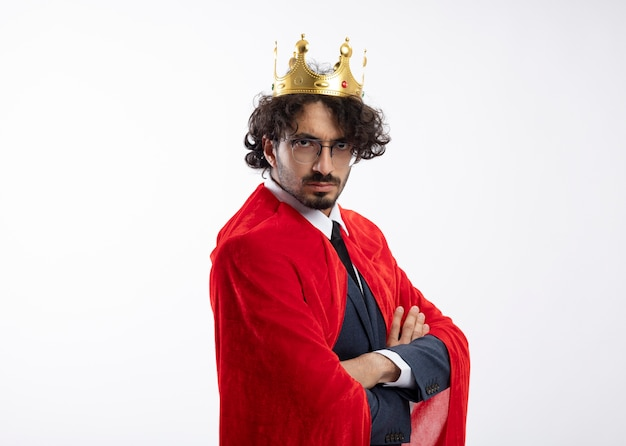 빨간 망토와 왕관과 함께 양복을 입고 광학 안경에 자신감이 젊은 백인 슈퍼 히어로 남자는 팔을 교차 옆으로 서