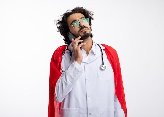 Fiducioso giovane caucasico supereroe uomo in occhiali ottici che indossa l'uniforme del medico con mantello rosso e con lo stetoscopio intorno al collo parla al telefono