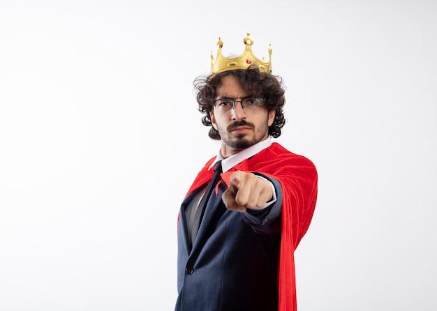 Fiducioso giovane supereroe caucasico uomo con occhiali ottici che indossa tuta con mantello rosso e punti corona alla telecamera