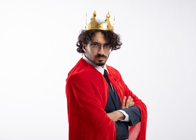 Fiducioso giovane supereroe caucasico uomo in occhiali ottici che indossa tuta con mantello rosso e corona si erge lateralmente con le braccia incrociate