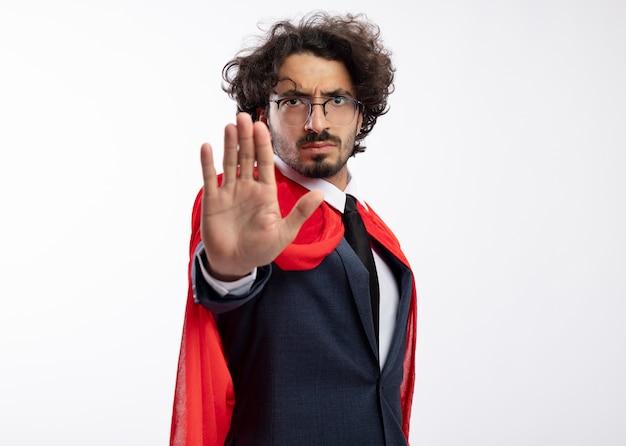 Fiducioso giovane supereroe caucasico uomo in occhiali ottici che indossa tuta con mantello rosso che gesturing il segno della mano di arresto