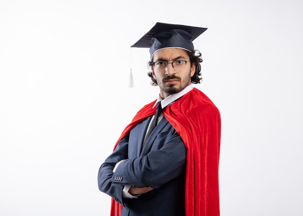 Fiducioso giovane supereroe caucasico uomo in occhiali ottici che indossa tuta con mantello rosso e cappello di laurea si leva in piedi lateralmente con le braccia incrociate guardando con lo spazio della copia