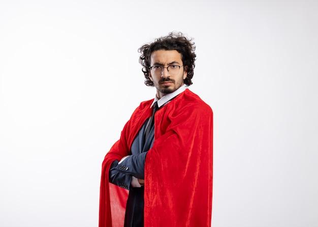Fiducioso giovane supereroe caucasico uomo in occhiali ottici che indossa un abito con mantello rosso si erge con le braccia incrociate