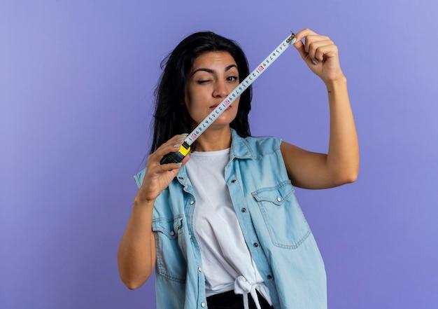 Fiduciosa giovane donna caucasica lampeggia gli occhi e tiene il metro a nastro isolato su sfondo viola con spazio di copia