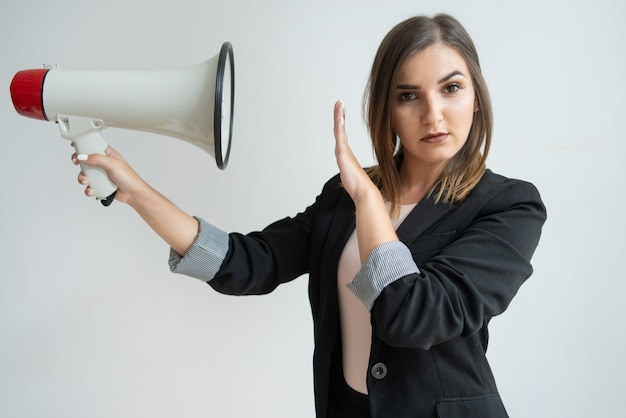 Confident young caucasian woman directing megaphone at herself