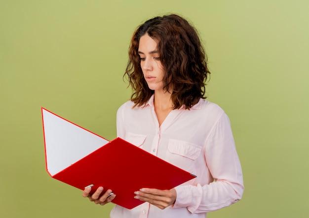 コピースペースと緑の背景に分離されたファイルフォルダを保持し、見て自信を持って若い白人女性