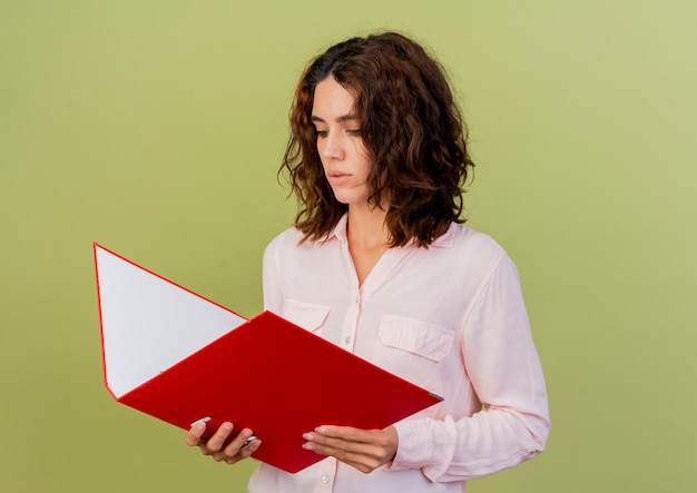 Confident young caucasian woman holding and looking at file folder isolated on green background with copy space