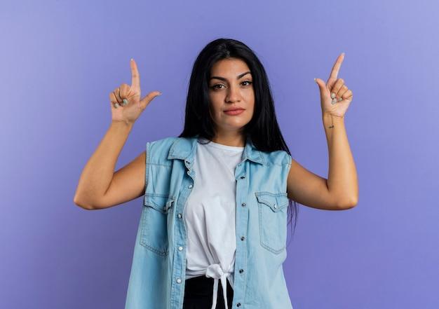 La giovane donna caucasica sicura indica con due mani isolate su fondo viola con lo spazio della copia