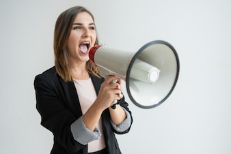 Confident young Caucasian woman shouting aside in megaphone
