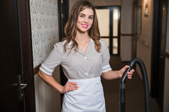Confident young chambermaid holding the vacuum cleaner pipe in the hotel