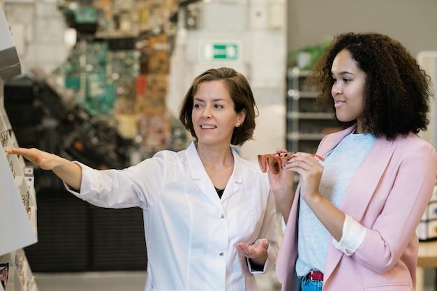 展示されている眼鏡の女性クライアントの新しいモデルを示すホワイトコートの自信を持って若いコンサルタント