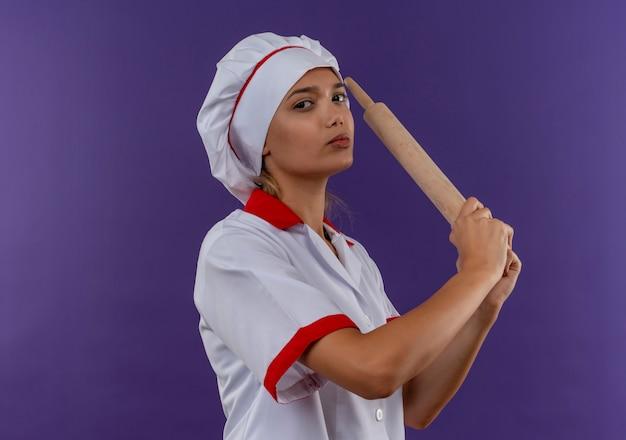 Уверенная молодая женщина-повар в униформе шеф-повара держит скалку на изолированной стене с копией пространства