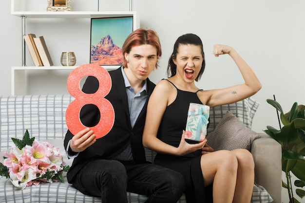 Confident young couple on happy women day holding number eight with present girl showing strong gesture sitting on sofa in living room
