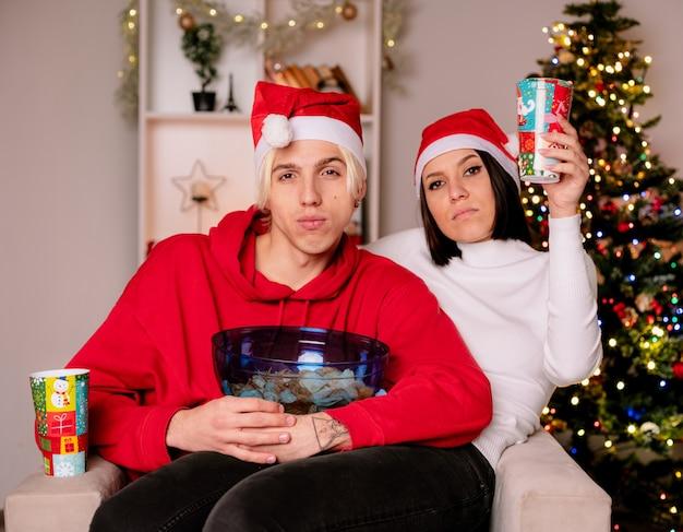 Fiducioso giovane coppia a casa nel periodo natalizio indossando il cappello di babbo natale seduto sulla poltrona ragazzo che tiene una ciotola di patatine ragazza con una tazza di plastica di natale entrambi guardando la telecamera in soggiorno