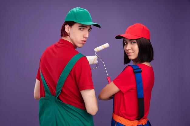 건설 노동자 유니폼을 입은 자신감 있는 젊은 부부와 페인트 롤러를 들고 뒤에 서 있는 모자