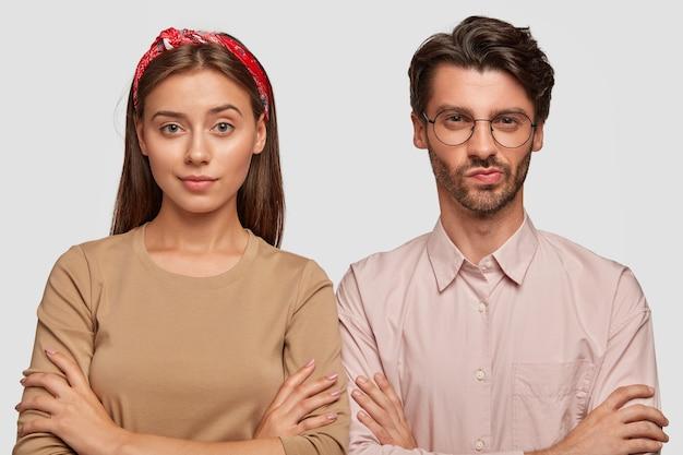 Уверенная в себе молодая пара позирует у белой стены