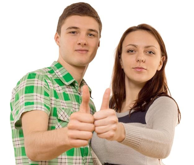 Уверенно молодая пара показывает палец вверх, на белом