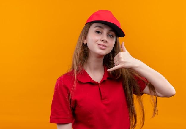 Уверенная молодая доставщица в красной форме делает жест вызова на изолированном оранжевом пространстве с копией пространства