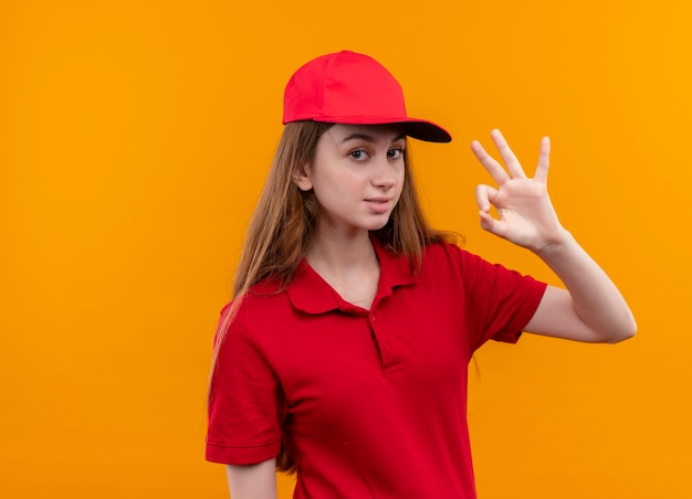 Уверенная молодая доставщица в красной форме делает хорошо, подписывается на изолированном оранжевом пространстве с копией пространства