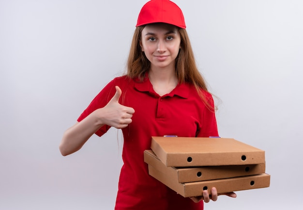 パッケージを保持し、孤立した白いスペースに親指を表示して赤い制服を着た自信を持って若い配達の女の子