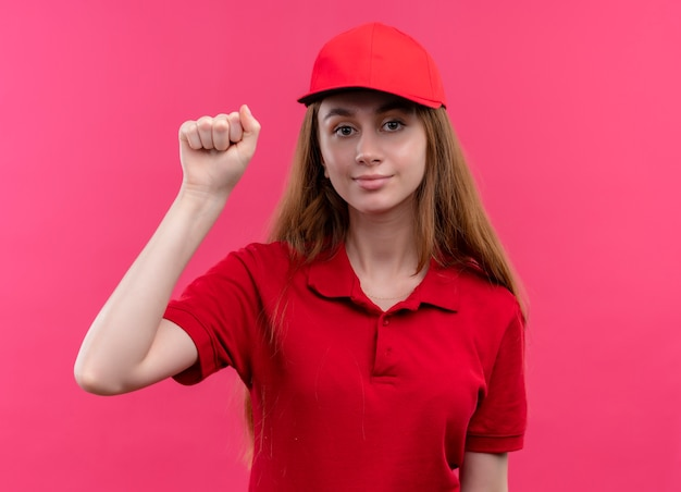Confident young delivery girl in red uniform doing knock gesture on isolated pink space