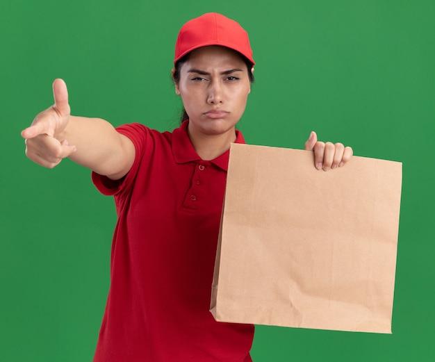 緑の壁に分離されたカメラで紙の食品パッケージ ポイントを保持している制服と帽子を着た自信のある若い配達の女の子