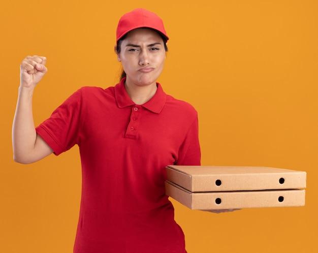 Fiduciosa giovane ragazza delle consegne che indossa l'uniforme e il cappuccio che tiene le scatole della pizza alzando il pugno isolato sulla parete arancione