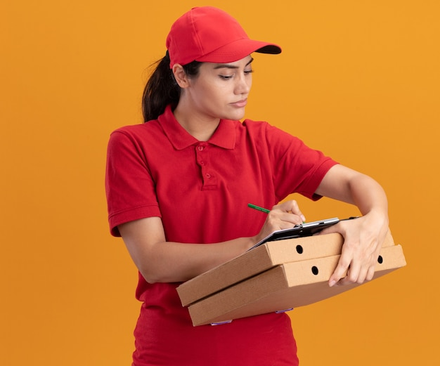 Confident young delivery girl wearing uniform and cap writing something on clipboard on pizza boxes isolated on orange wall