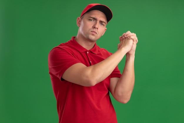 Уверенный молодой курьер в униформе и кепке, показывающий жест рукопожатия, изолированный на зеленой стене