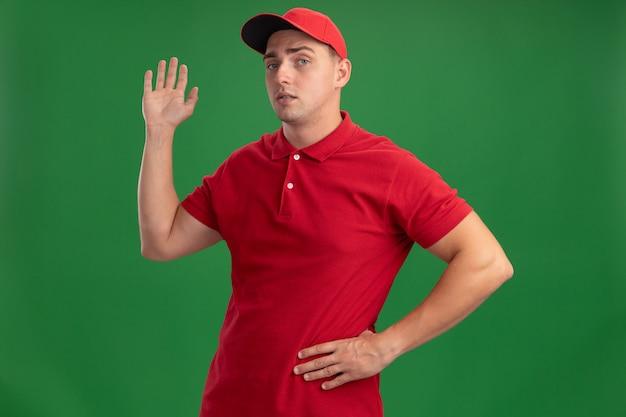 緑の壁に隔離された腰に手を置くハロージェスチャーを示す制服とキャップを身に着けている自信を持って若い配達人