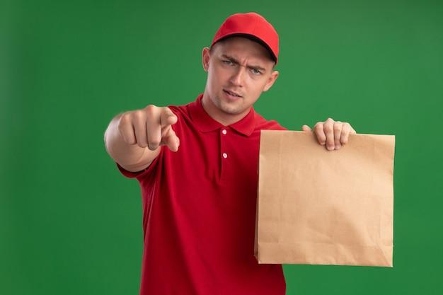 拿着纸食物包裹的确信的年轻送货人佩带的制服和盖帽显示您的姿态在绿色墙壁上隔绝