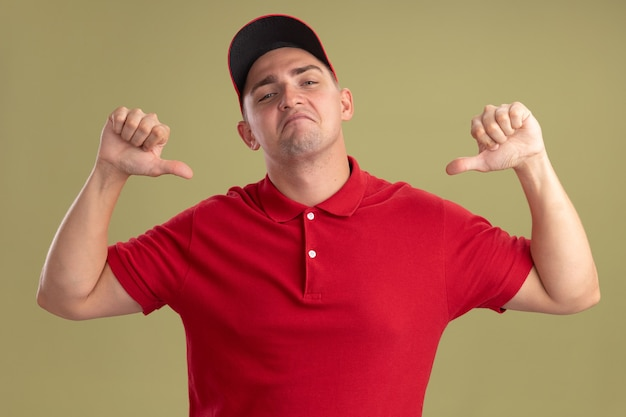 Confident young delivery man wearing uniform and cap points at himself isolated on olive green wall