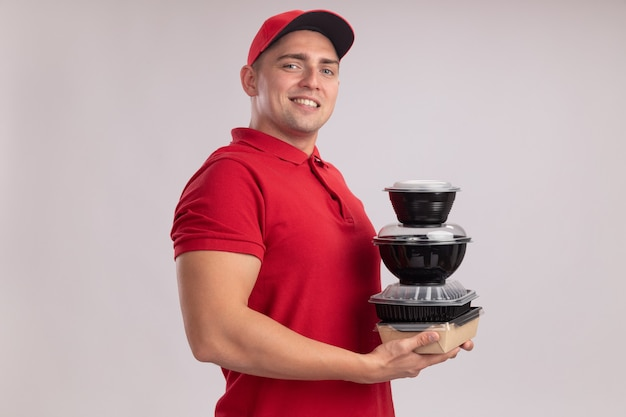 Fiducioso giovane uomo di consegna indossando l'uniforme con tappo che tiene contenitori per alimenti isolati sulla parete bianca