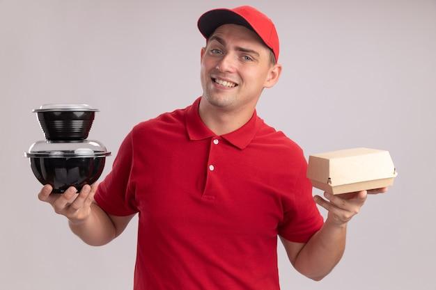 Fiducioso giovane uomo di consegna che indossa l'uniforme con cappuccio che tiene il pacchetto di cibo di carta con contenitore per alimenti isolato sulla parete bianca
