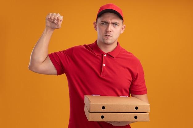 오렌지 벽에 고립 된 강한 제스처를 보여주는 피자 상자를 들고 모자와 유니폼을 입고 자신감 젊은 배달 남자