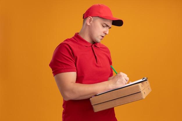 Fiducioso giovane fattorino che indossa l'uniforme con cappuccio tenendo le scatole per pizza e scrivendo qualcosa negli appunti isolato sulla parete arancione