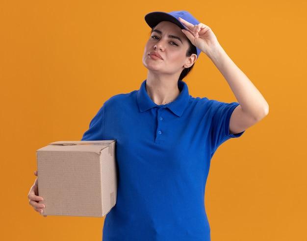 제복을 입은 자신감 있는 젊은 배달 여성과 카드박스를 들고 있는 모자