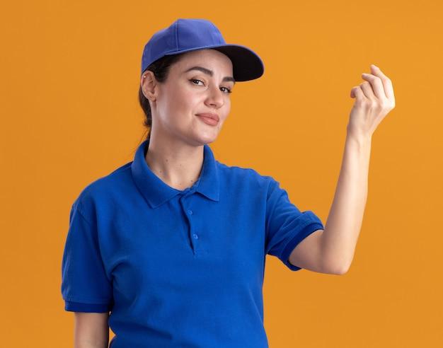 Fiduciosa giovane donna delle consegne in uniforme e berretto che fa un gesto di denaro
